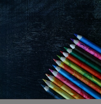 暗い背景に明るい色鉛筆コピースペースで学校と教育のモックアップに戻る