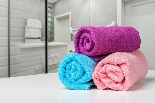 Bright colored towel on a shelf in a bathroom
