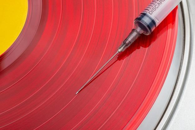 의료용 바늘로 회전하는 밝은 색상의 비닐 레코드