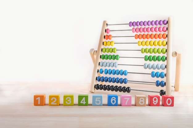 Bright colored wooden bricks with numbers and abacus toy with copy space