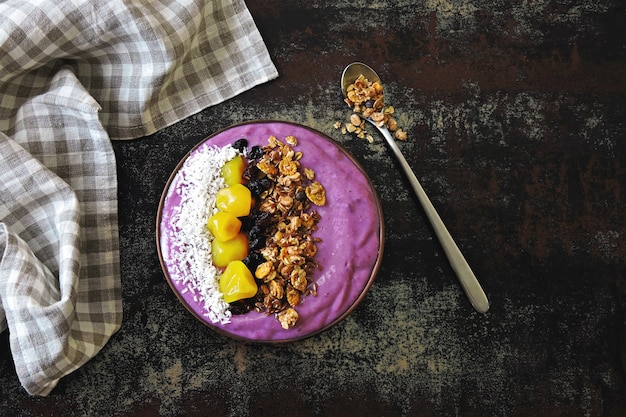 Bright colorful acai bowl with granola and dried fruit.
