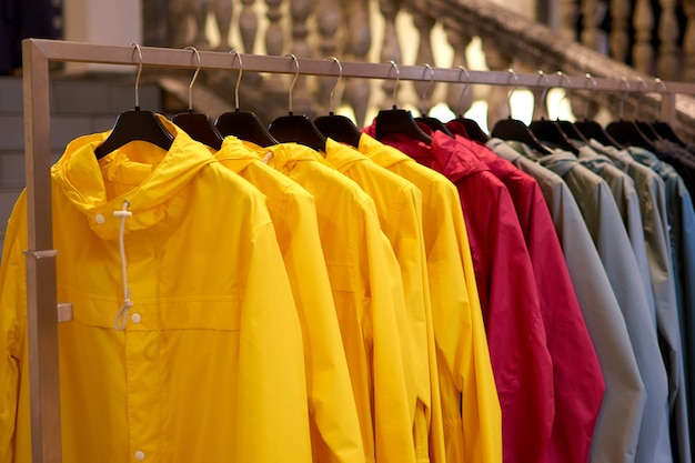 Bright colorful autumn raincoats hanging at a fashion store.