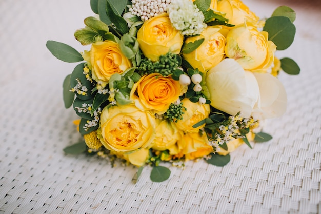 Bright and colorful autumn wedding bouquet with yellow roses, white peonie.