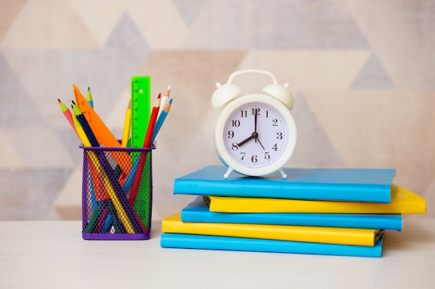 Bright colorful books, alarm clock and colored pencils on a light background. back to school.