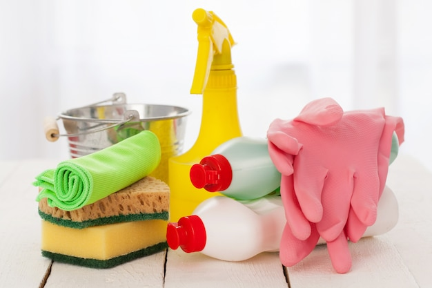 Bright colorful cleaning set on a wooden table Free Photo