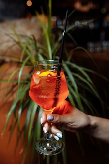 Bright and colorful cocktail aperol spritz in a waiter hand in a glove against a background of greenery.