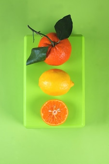 Bright colorful flat lay of tangerines, lemons and tropical leaves