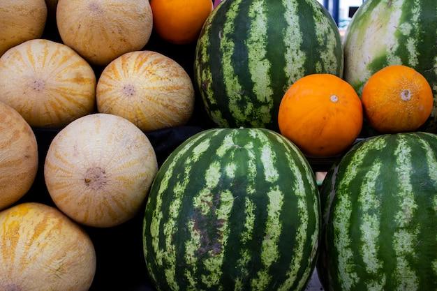 ファーマーズマーケットのスイカ、メロンのカウンターに明るくカラフルな果物