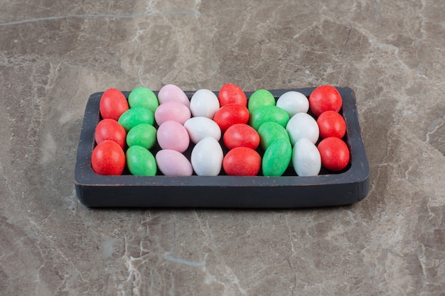 Яркие красочные мармеладки. раздельные цвета на деревянной тарелке.