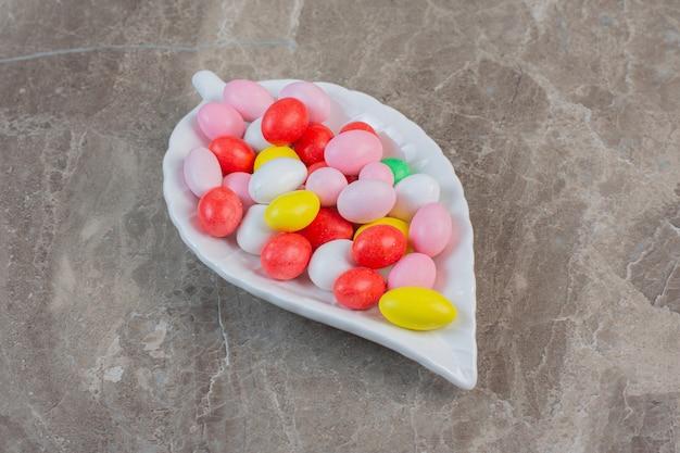 Яркие красочные мармеладки красного, зеленого, розового, синего, желтого и белого цветов. в белой тарелке.