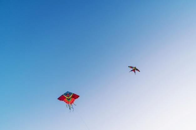 青い澄んだ空を飛んでいる明るくカラフルな凧