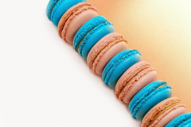 Bright colorful macaroons cakes on a white background with copy space.