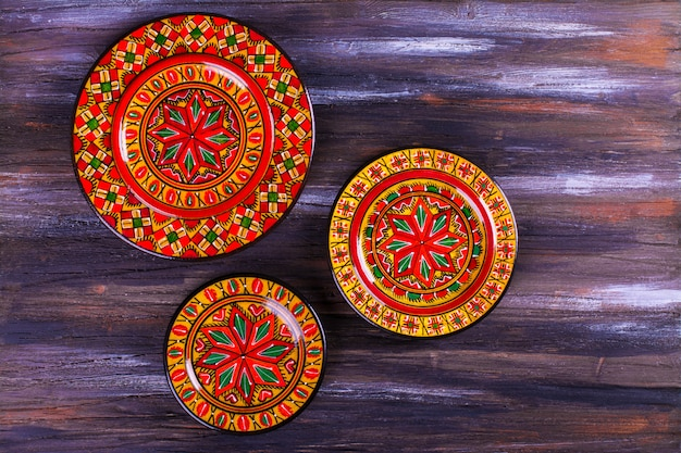Bright colorful plates on wooden multicolor background