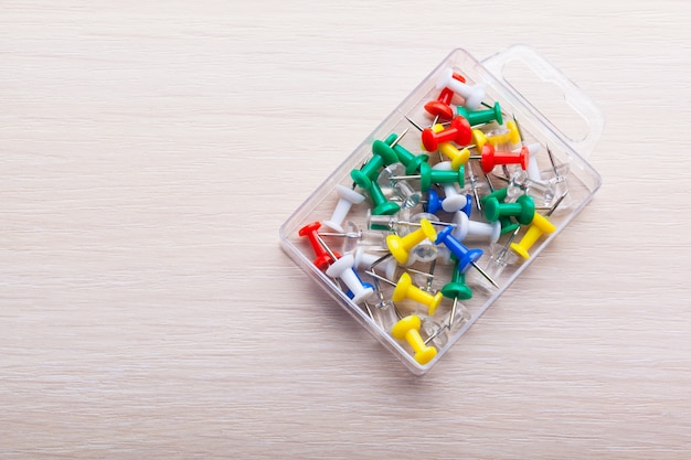 Bright colorful push pins on wooden table