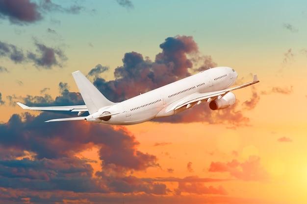 밝고 화려한 하늘과 일몰에 날아가는 비행기.