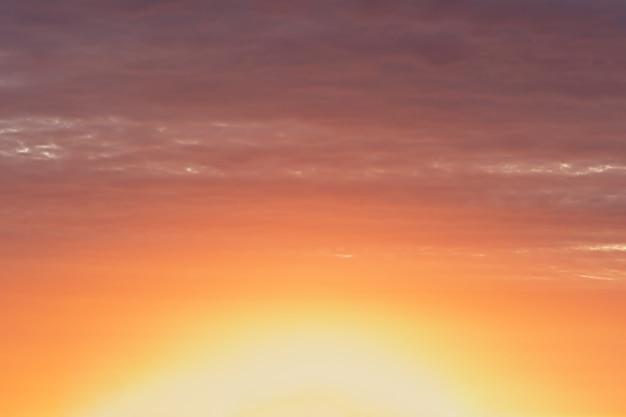オレンジピンクと紫の色で日没時の明るくカラフルな空。