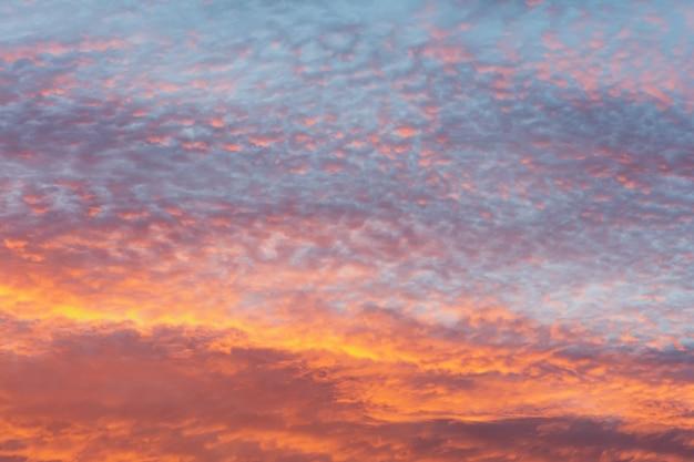 オレンジ、ピンク、紫、青の色で日没時の明るくカラフルな空。