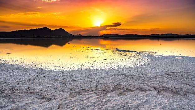 소금 호수에 밝고 화려한 일몰