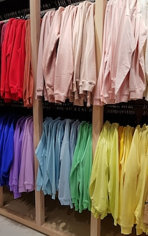 ファッション店にぶら下がっている明るくカラフルなスウェットシャツ。マルチカラーの黄色、赤、灰色のクローズアップ、