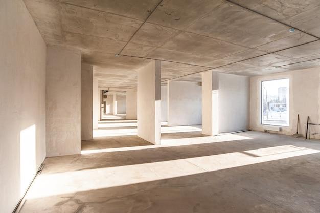 Светлая коммерческая недвижимость без отделки с оштукатуренными окнами
