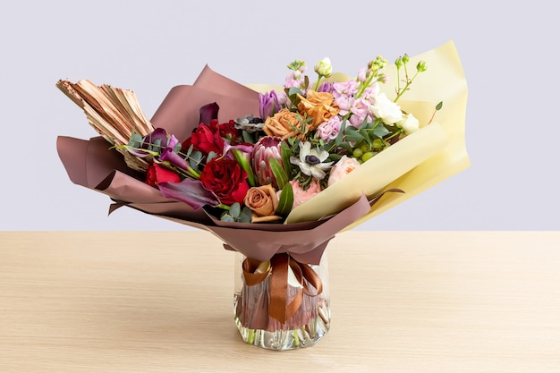 Bright composite bouquet of proteus, multi-colored roses, anemone, eucalyptus and calla in a vase on a light desk.