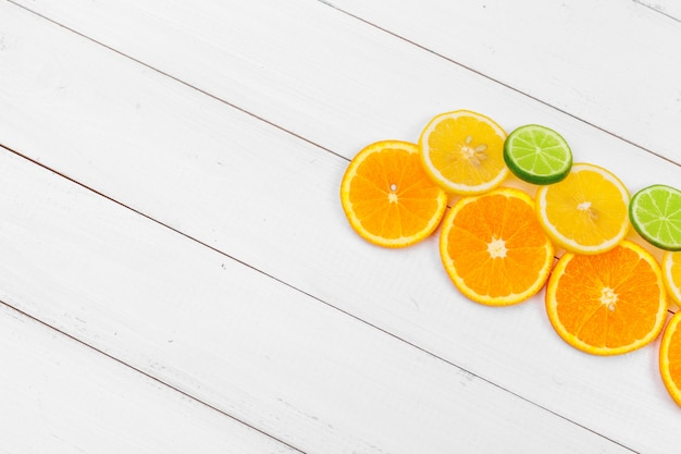 Bright composition of citrus fruits on white wooden background