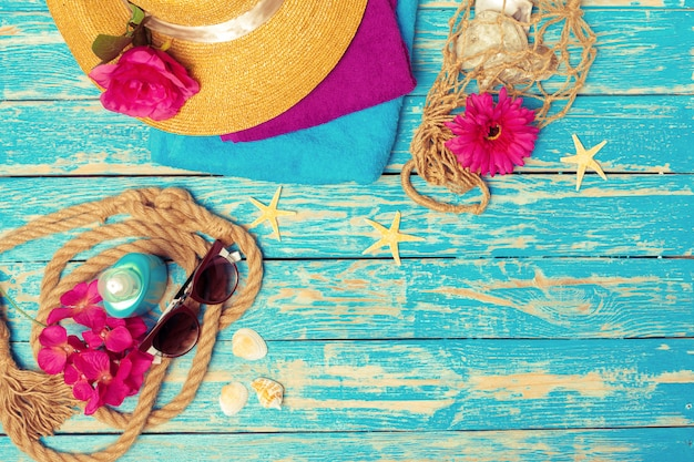 Bright composition of female  beach accessories on blue wooden