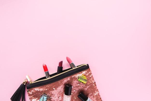 ファッションアクセサリーの明るい構成。マニキュア、口紅、ヘアピンが付いたキラキラスパンコールコスメティックバッグ。柔らかいパステル調の背景のオブジェクト。フラットレイ、上面図。