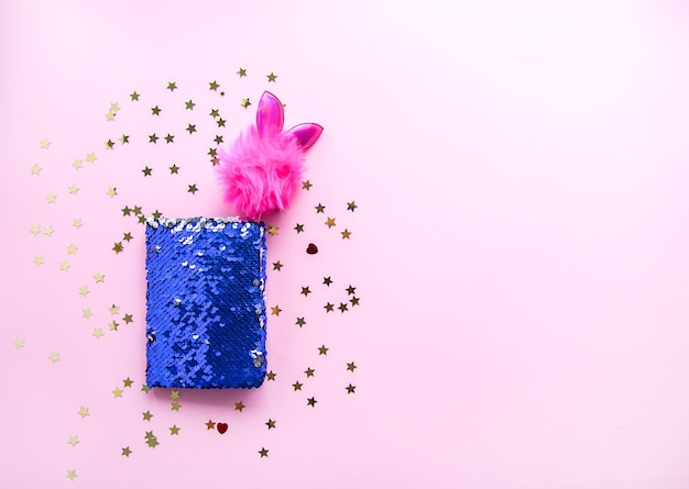 Яркая композиция модных аксессуаров. сумочка с блестками, блокнот, забавная ручка и декоративная мишура на мягком пастельном фоне. плоская планировка, вид сверху.