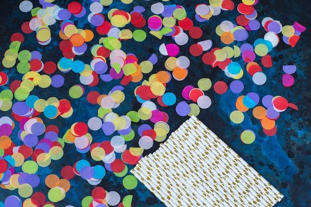 Яркие конфетти и коктейльные трубочки на синем фоне