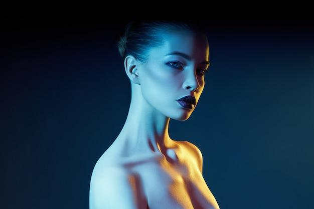 青と赤のシャドウトーンの女性の明るく対照的な美容化粧肖像画。完璧な清潔な肌と顔のメイク、ふっくらとした唇に濃い口紅