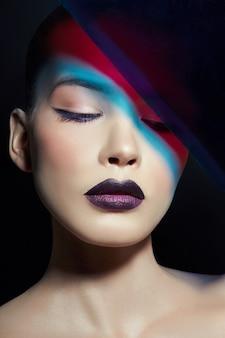 Яркий контрастный красоты макияж портрета женщины в синих и красных теневых тонах