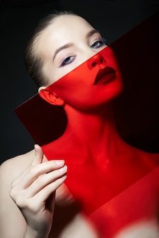 Bright contrasting beauty makeup portrait of a woman in blue and red shadow tones.