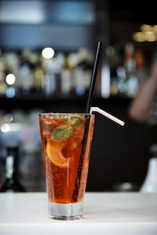 A bright cool cocktail with bubbles and straws on a dark background of a blurred bar.