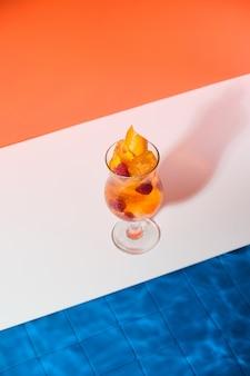 수영장 옆에서 라즈베리와 얼음 조각을 곁들인 밝고 시원한 오렌지 칵테일 토닝 상쾌한 음료