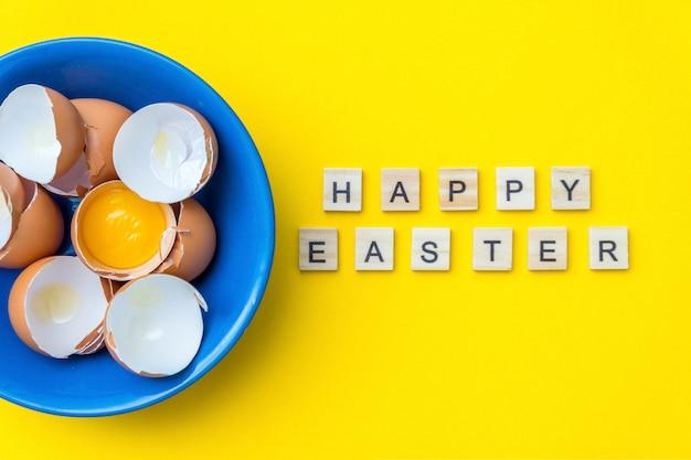 ハッピーイースターのテキストと明るい創造的なはがき。生卵、卵黄、黄色の表面に青いプレートのシェル