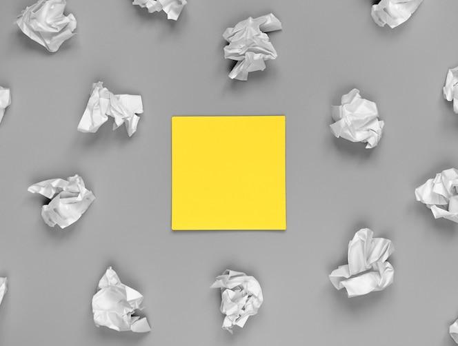 明亮的创造力概念,黄色贴纸和皱巴巴的纸。背景中的背景