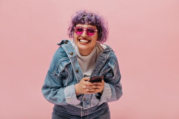 세련된 분홍색 안경, 데님 재킷 및 청바지에 라일락 머리를 가진 밝은 곱슬 여자는 그녀의 스마트 폰을 보유하고 있습니다
