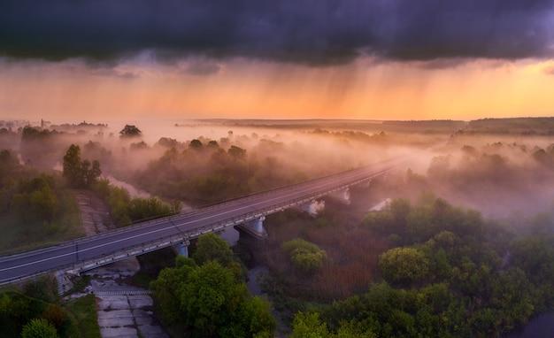 高速道路と川の牧草地の陸橋の上の明るい夜明けと嵐の雲。絵のように美しい場所への旅行のコンセプト。ドローンからの眺め。