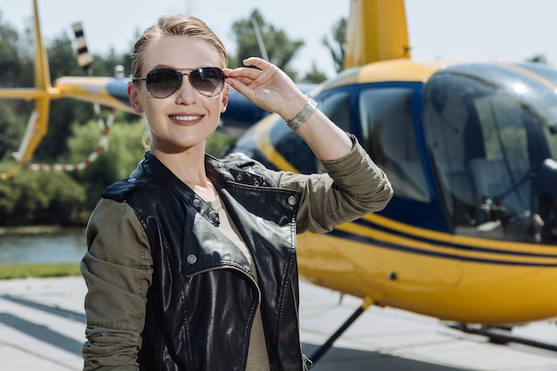 Bright day. cheerful female pilot posing for the camera and smiling while standing near the helicopter and starting her working day