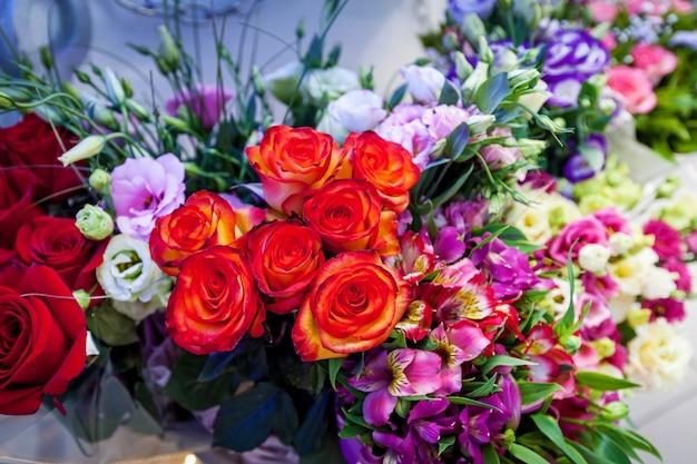 結婚式のテーブルの上の花の明るい装飾カラフルな赤のグループ