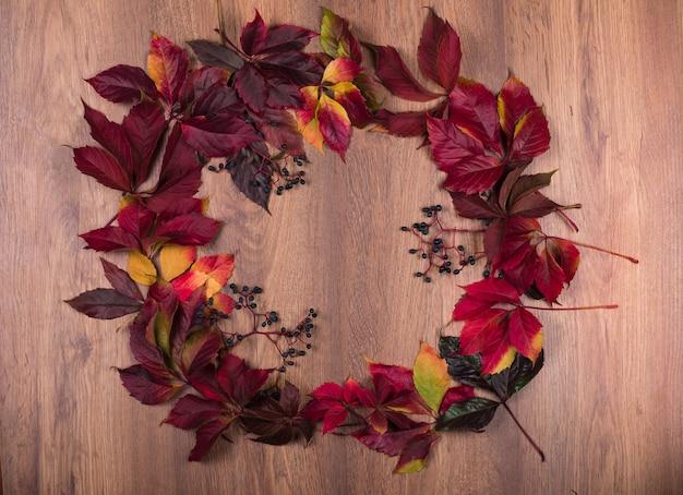 Яркий декоративный венок из разноцветных листьев дикого винограда на деревянном фоне с пространством для текста