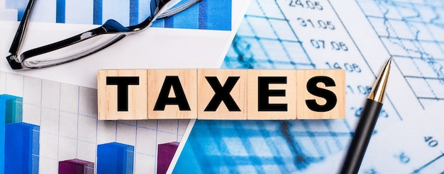 On the bright diagrams, glasses, a pen and wooden cubes with the word taxes. business concept