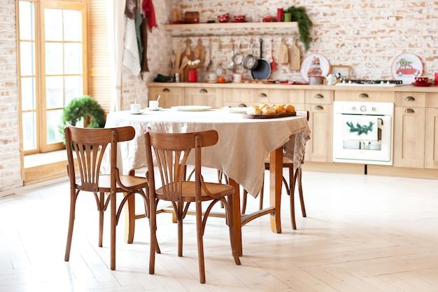 クリスマスのために装飾された家の中に木製のダイニングテーブル、椅子、キッチンのある明るいダイニングルーム