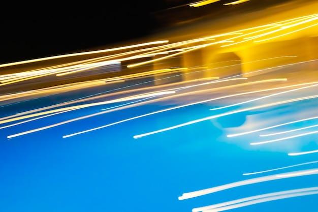 黒-黄-青の背景に明るい直接的な白と黄色のライトストリップ。