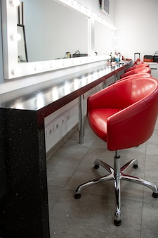 Bright dressing room with red chairs. a simple room for make-up several comfortable chairs are in a row.