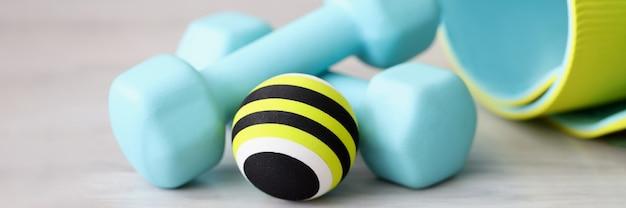 Яркие шары гантелей на спортивном коврике лежат на полу крупным планом