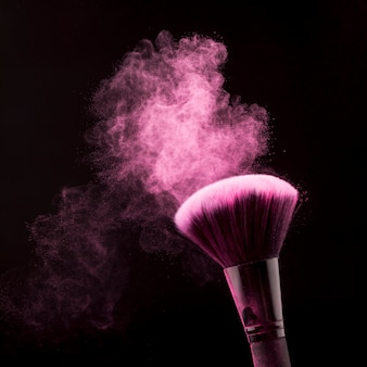 Bright dust of powder and brush for makeup on black background