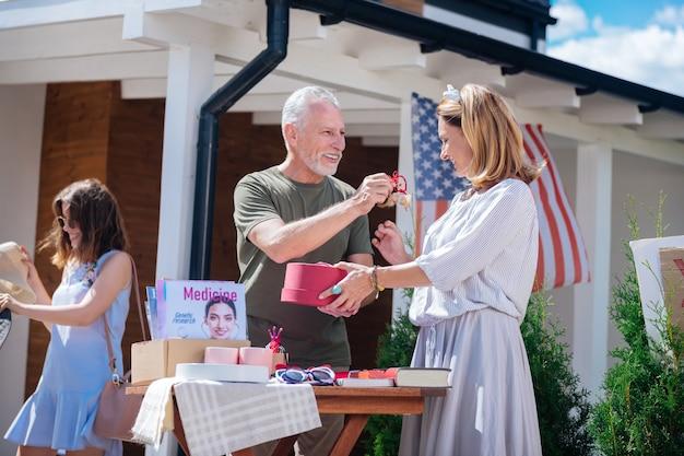 Яркие серьги. темноглазый бородатый мужчина показывает красивую женщину в полосатом платье с яркими серьгами на распродаже во дворе