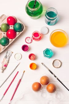 Bright easter eggs in containers near brushes and dye liquid in cans